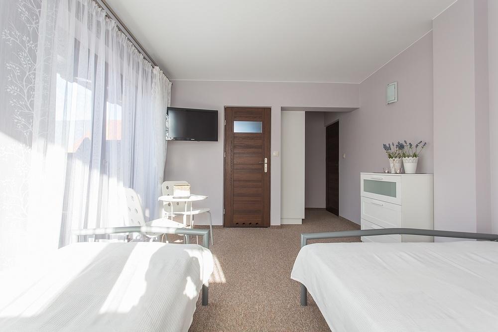 Łóżko małżeńskie i pojedyncze w jasnym pokoju
